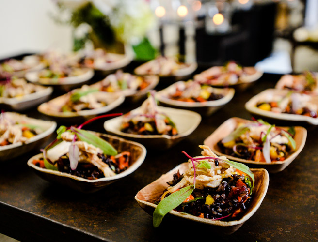 A table with several bowls of black bean salad to be served at a corporate catering event.