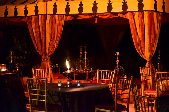 Outdoor dining with a red and yellow tent and tables with candles on them.