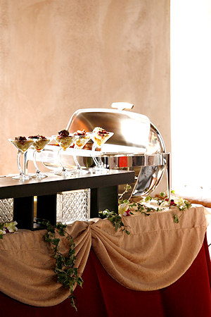A silver chaffing dish at the end of a catering food service line.