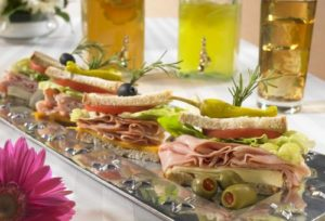 Corporate catering sandwich bar with bread, ham olives with toothpicks holding it together.