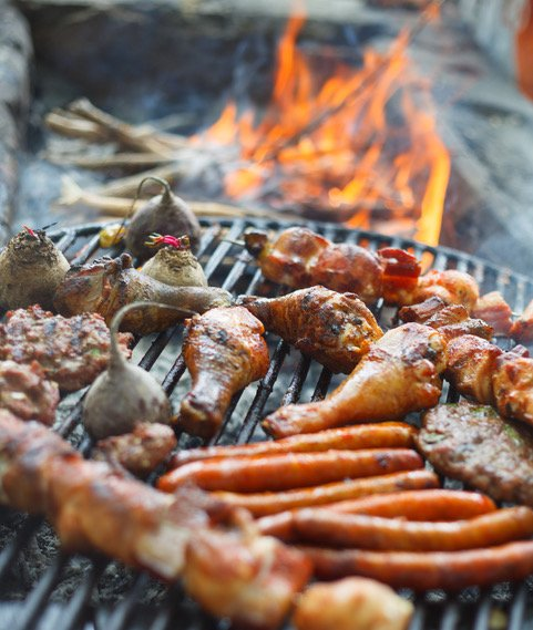 Bbq grill with sausages, chicken, skewers, and various meats over a flame.
